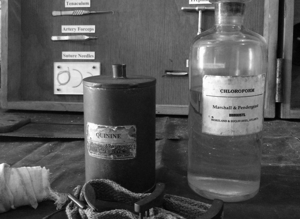 """Symbolbild für """"Mutterschoß"""": Foto mit altertümlichem Medizinbesteck und Medikamentflaschen u.a. mit Chloroform in schwarz/weiß"""