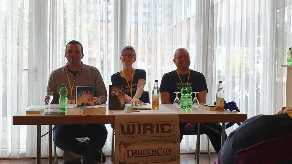 Lesung auf dem BuCon, drei Personen an einem Tisch präsentieren ihre Bücher, von links James Sullivan, Judith Vogt und Christian Vogt