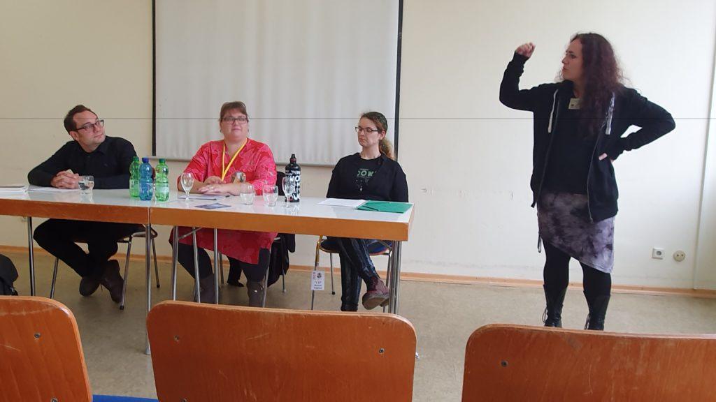 Lesung auf dem BuCon, drei Personen an einem Tisch, von links Robert von Cube, Veronika Lackerbauer, Melanie Vogltanz, daneben Verlegerin Ingrid Pointecker
