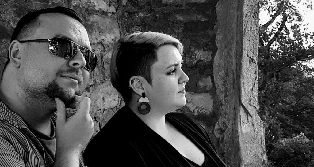 """Zwei Personen vor einer Maueröffnung, links Philipp, rechts Elea, beide Co-Hosts bei """"Der nerdige Trashtalk""""; sie blicken in die Ferne"""