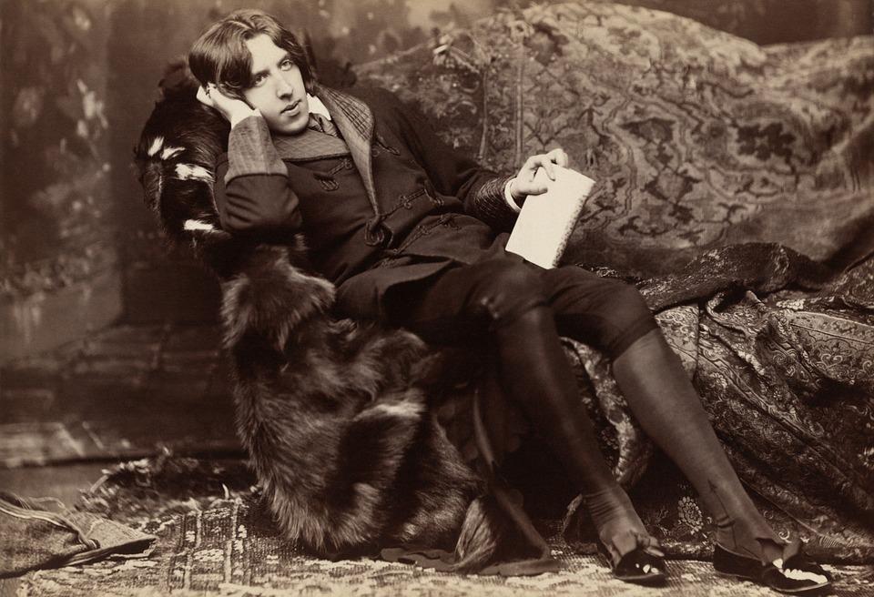 Foto des jungen Oscar Wilde, der in einem Sessel sitzt und nachdenklich in die Ferne blickt, in der Hand einen Notizblock