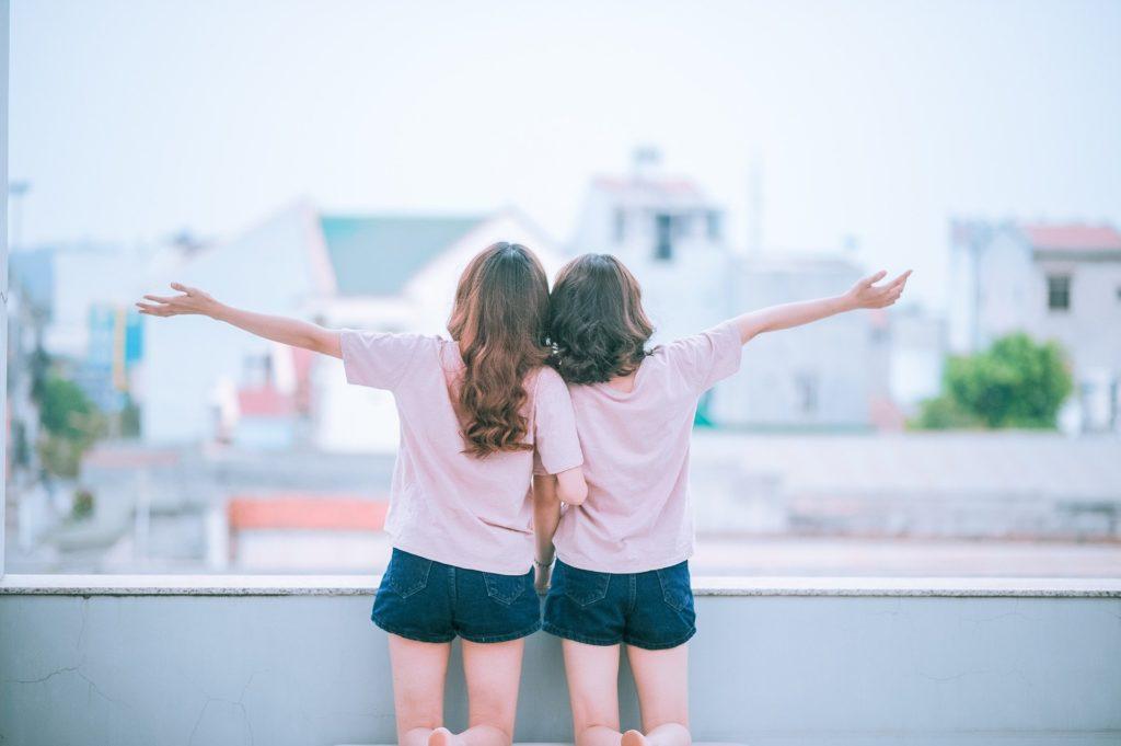 Zwei Frauen im Partnerlook stehen aneinander gelehnt mit dem Rücken zum Betrachter und breiten glücklich die Arme aus.